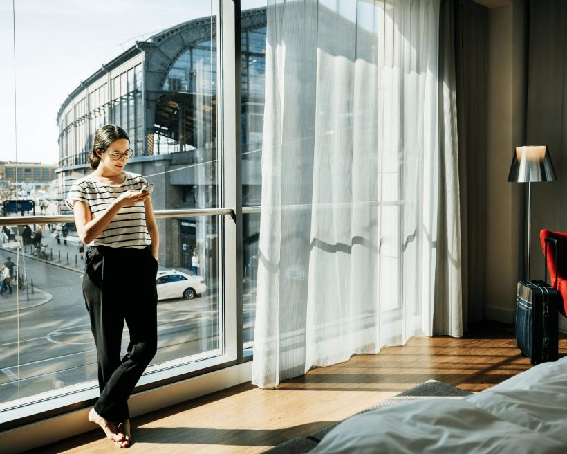 Business traveler leaning against floor to ceiling window of her spacious hotel room.