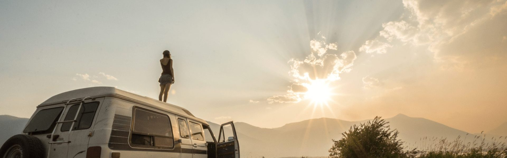A woman stands on top of her van at sunset.
